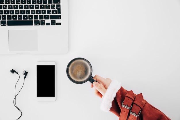 Крупным планом женская рука держит чашку кофе на рабочий стол с ноутбуком; мобильный телефон и наушники