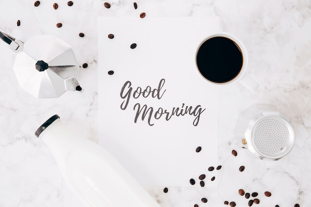 Поднятый вид текста доброго утра на бумаге; кафетерий кофейник; чашка кофе; бутылка молока и кофейные зерна на мраморном фоне