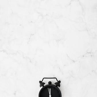 大理石の織り目加工の机の上の黒い目覚まし時計のクローズアップ