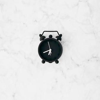白の織り目加工の壁紙に黒の目覚まし時計の高架ビュー