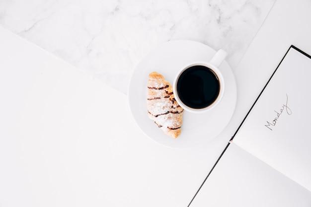 コーヒーカップとクロワッサンの白い机の上の日記の月曜日のテキスト