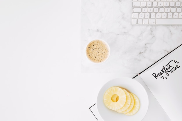 キーボードで紙の上の朝食時のテキスト。パイナップルスライスと机の上のコーヒーカップ