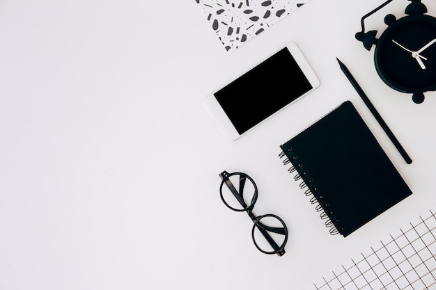 Поднятый вид на будильник; сотовый телефон; дневник; карандашная бумага и очки на белом фоне