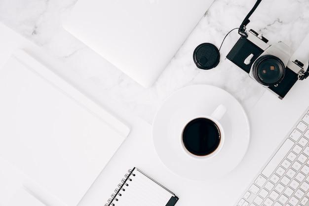 Поднятый вид дневника; цифровой планшет; чашка кофе; камера и клавиатура на столе