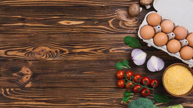 卵のカートン。キノコ;ポレンタ;玉ねぎとブロッコリーの木製の机の上
