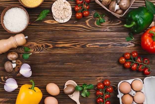 新鮮な野菜と米の穀物の木製の机の上の創造的なレイアウト