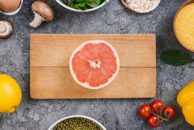 グレーのコンクリート背景に野菜に囲まれた木製のまな板に半分グレープフルーツ