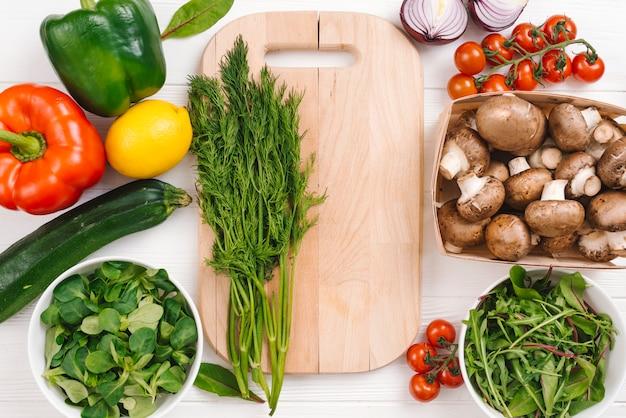 新鮮な野菜と木製のまな板