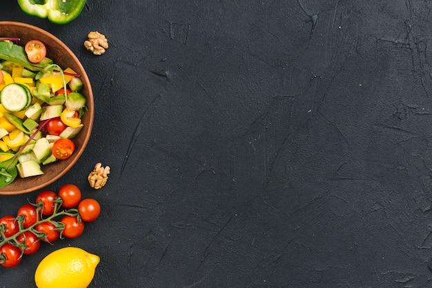 黒のコンクリートの背景にクルミと新鮮野菜のサラダ