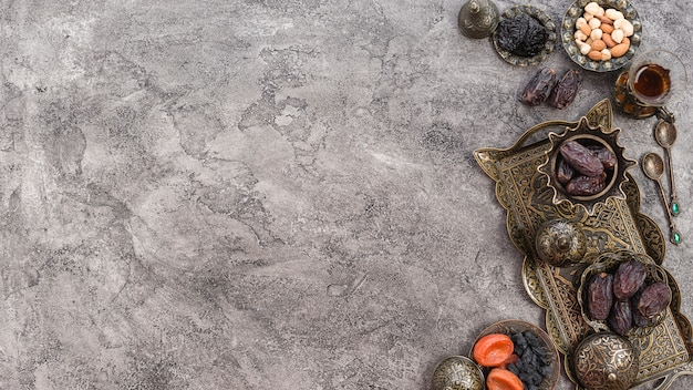 Повышенный вид дат; орехи и изюм на металлическом подносе на сером бетонном фоне