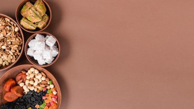 Земляные чаши с орехами; сухофрукты; лукум и пахлава на коричневом фоне