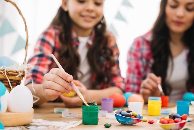 Размытые мать и дочь, роспись пасхальных яиц на столе