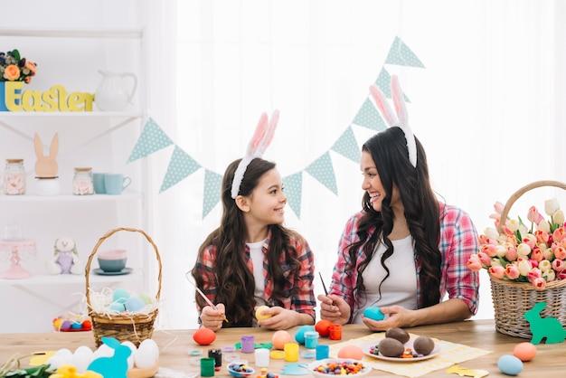 幸せな母と娘の家でブラシでイースターエッグを塗る