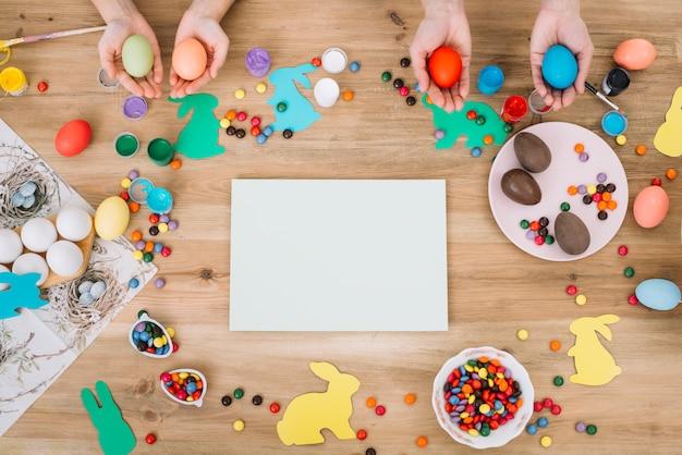 木製のテーブルの上にカラフルなキャンディーとホワイトペーパーでイースターエッグを両手