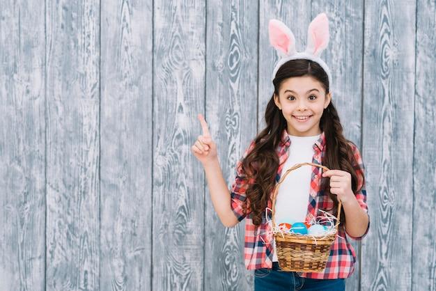 カメラを探してバスケットポインティング指でイースターの卵を持って微笑んでいる女の子