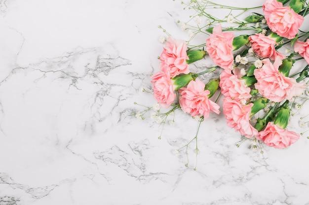 大理石の織り目加工の背景の隅に赤ちゃんの息の花とカーネーションの花束