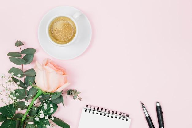 Кофе; цветок роза; блокнот и авторучка на розовом фоне