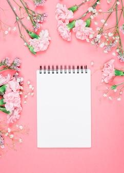 カーネーションで飾られた空白のスパイラルメモ帳。ジプソフィラ。ピンクの背景にリモニウムの花