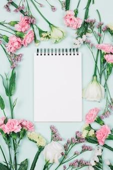 リモニウムに囲まれた空白のスパイラルメモ帳。カーネーションとトルコギキョウの花青い背景
