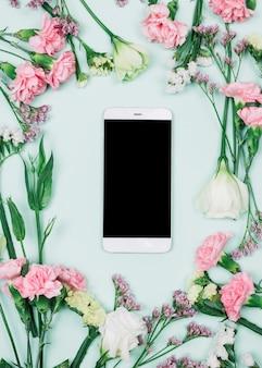新鮮なリモニウムに囲まれた空白のスマートフォン。カーネーションとトルコギキョウの花青い背景