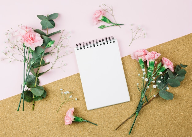 デュアルピンクと段ボールの背景に石膏とカーネーションの花に囲まれたスパイラルメモ帳の俯瞰