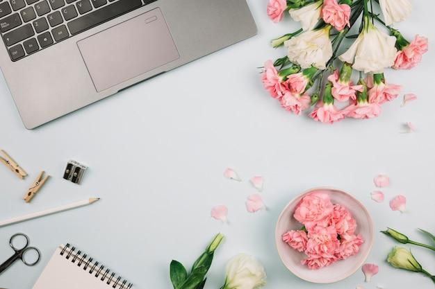 ラップトップ上のカーネーションとトルコギキョウの花。鉛筆;はさみ;研ぎ器と青い机の上のスパイラルメモ帳