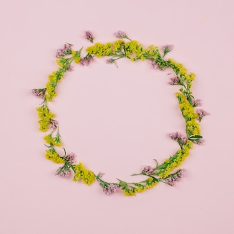 Круглая пустая рамка из розового золота с лимониумом и желтыми золотарниками или солидаго гигантскими цветами
