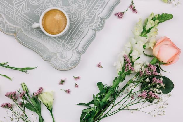 Кофейная чашка на подносе с лимониумом; роза; эустома и цветок львиного зева на белом фоне