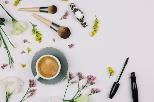 Чашка кофе; наручные часы; косметическая кисточка; тушь для ресниц со свежими цветами на белом фоне