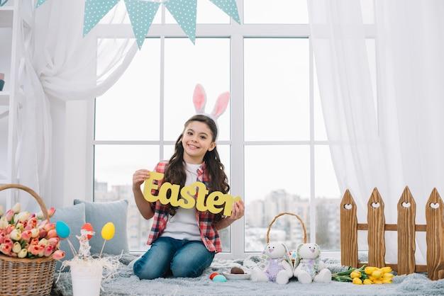 Портрет улыбающейся девушки, сидя перед окном, показывая желтое пасхальное слово