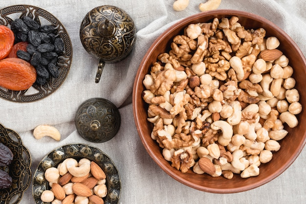 Выгравированная круглая чаша с орехами; умершие фрукты и миску орехов на скатерти