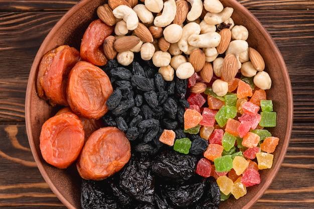 Повышенный вид абрикоса; сухофрукты; черный изюм и орехи в миске на деревянной поверхности