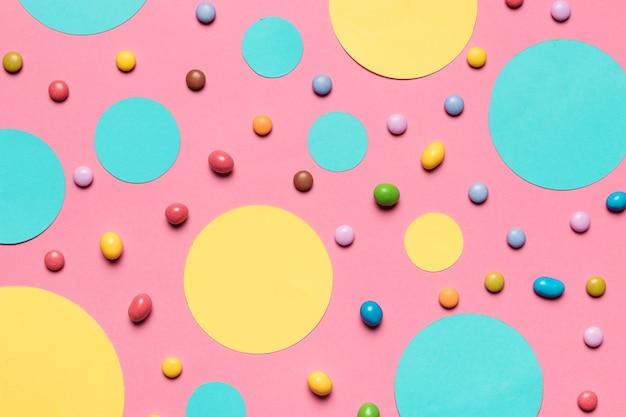 Бирюзовые и желтые круглые рамки с разноцветными конфетами на розовом фоне