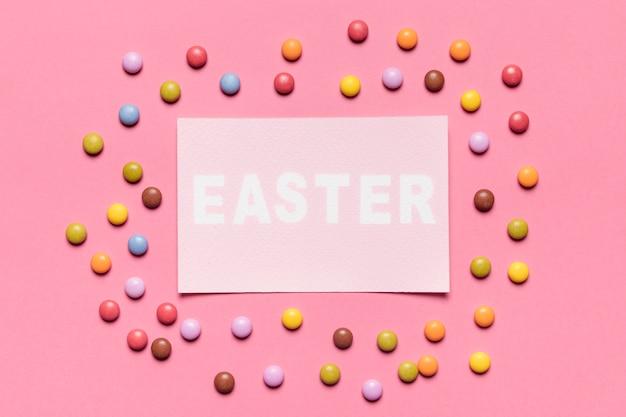 ピンクの背景にイースターの言葉で紙の周りに囲まれたカラフルな宝石キャンディー
