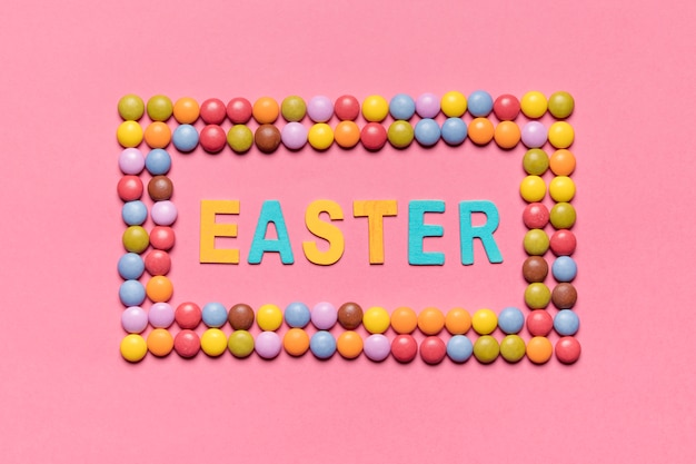 ピンクの背景の上のカラフルな宝石キャンディーフレーム内のイースターの言葉