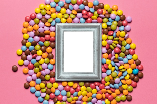 ピンクの背景にカラフルな宝石キャンディーの上の空のシルバーフレーム