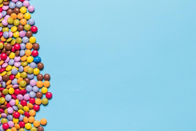 青い背景の側にカラフルな宝石キャンディー