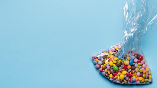 Разноцветные драгоценные конфеты в полиэтиленовом пакете на синем фоне