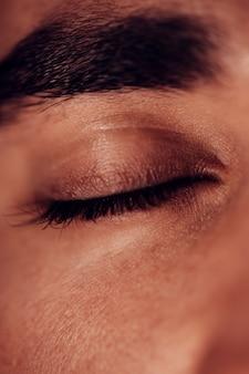 Закрытый глаз с темными бровями