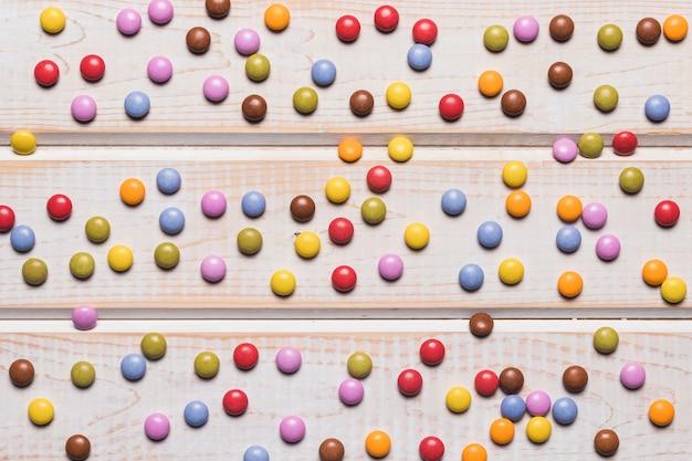 木製の机の上の色とりどりの宝石キャンディーのフルフレーム