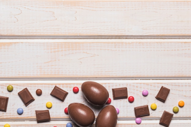 チョコレートのかけらイースターエッグと木製の机の下の宝石のお菓子