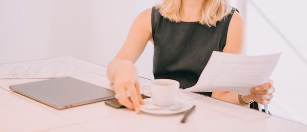職場で一杯のコーヒーを持って手で文書用紙を持って若い実業家