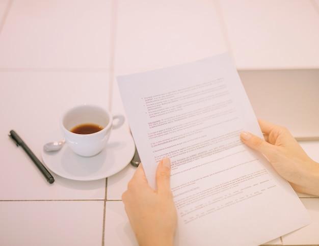 ペンとテーブルの上のコーヒーカップと手で文書を持っている実業家の手のクローズアップ