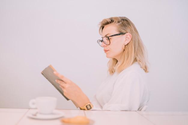Завтрак перед молодой женщиной, читающей книгу