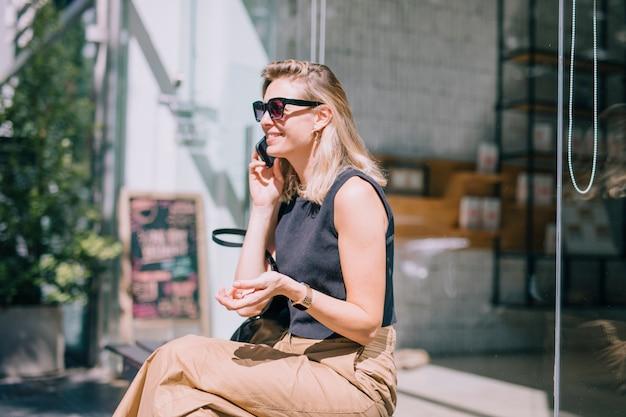Улыбается молодая женщина, сидя за пределами магазина, разговаривает по мобильному телефону