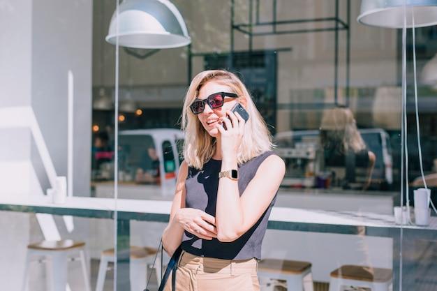 Портрет привлекательной молодой женщины, стоя перед магазином, разговор по мобильному телефону