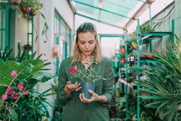 Молодая взрослая женщина работает в садоводческом магазине