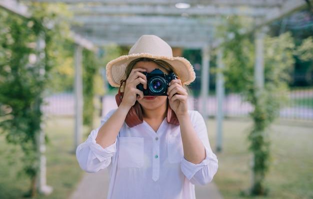 Шляпа молодой женщины нося фотографируя с камерой