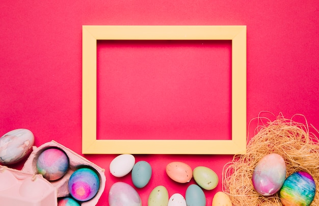 Пустая желтая рамка с красочными пасхальными яйцами на розовом фоне