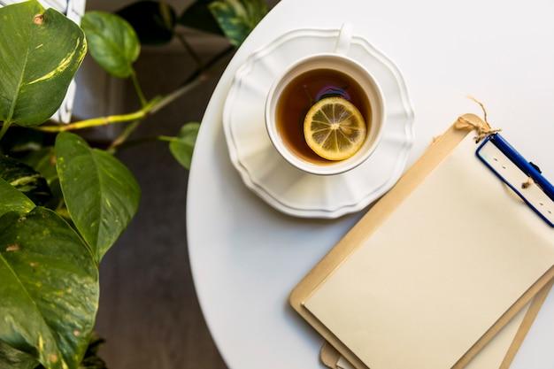 Чашка чая и чистый лист бумаги прикрепить в буфер обмена на белом столе